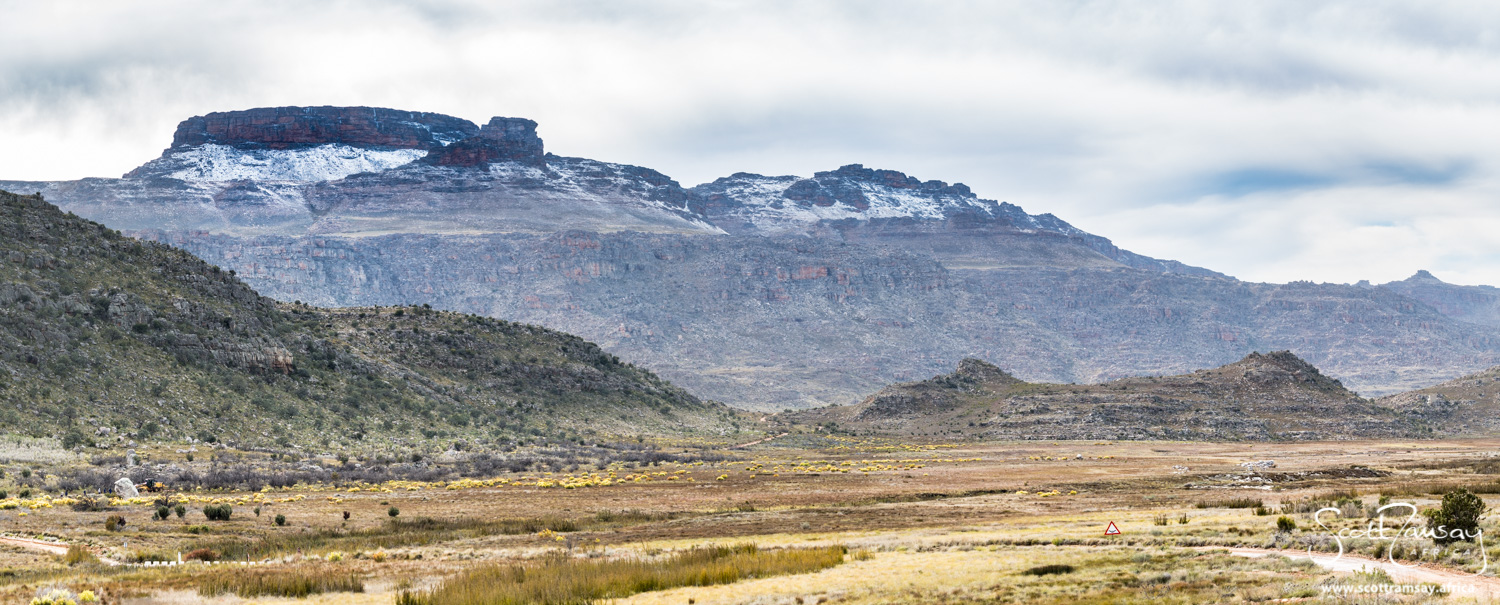 The road to Driehoek Farm, at the top of Uitkyk Pass. Tafelberg Mountain bedecked with snow rises to almost 2000 metres.