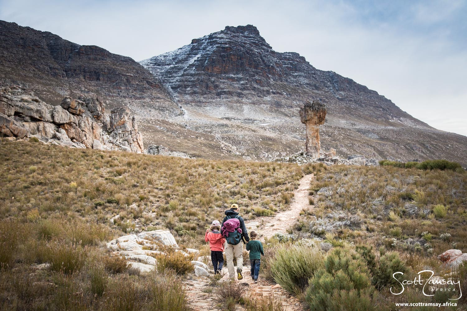 Friends Steve, Azara and Gabriel Davis approaching the Maltese Cross, with Sneeuberg rising to almost 2 000 metres on the horizon. Note the sprinkling of snow - winters in the Cederberg can be cold!