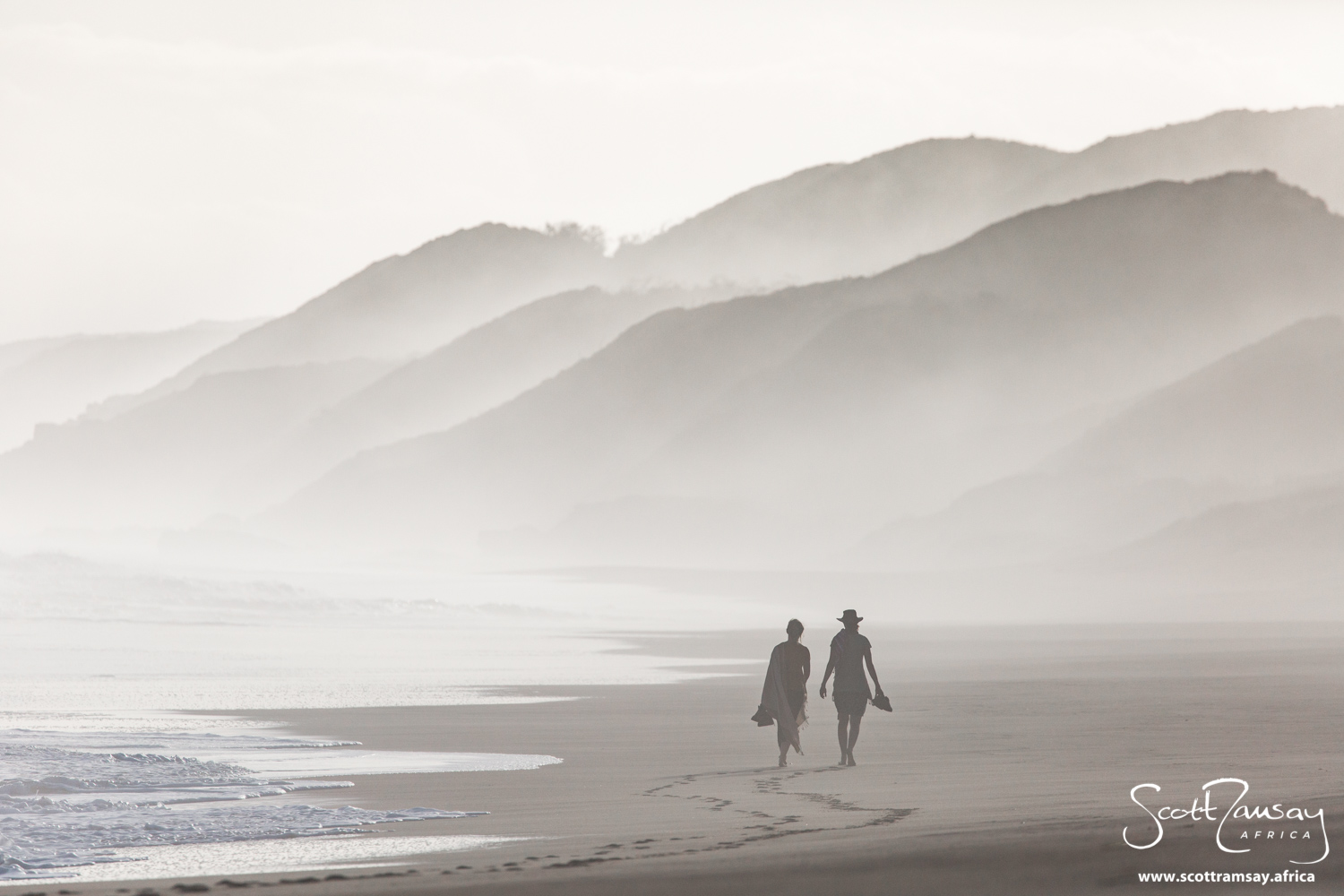 Joni and Helen walking along the ocean shoreline of Goukamma, with the high vegetated dunes in the background