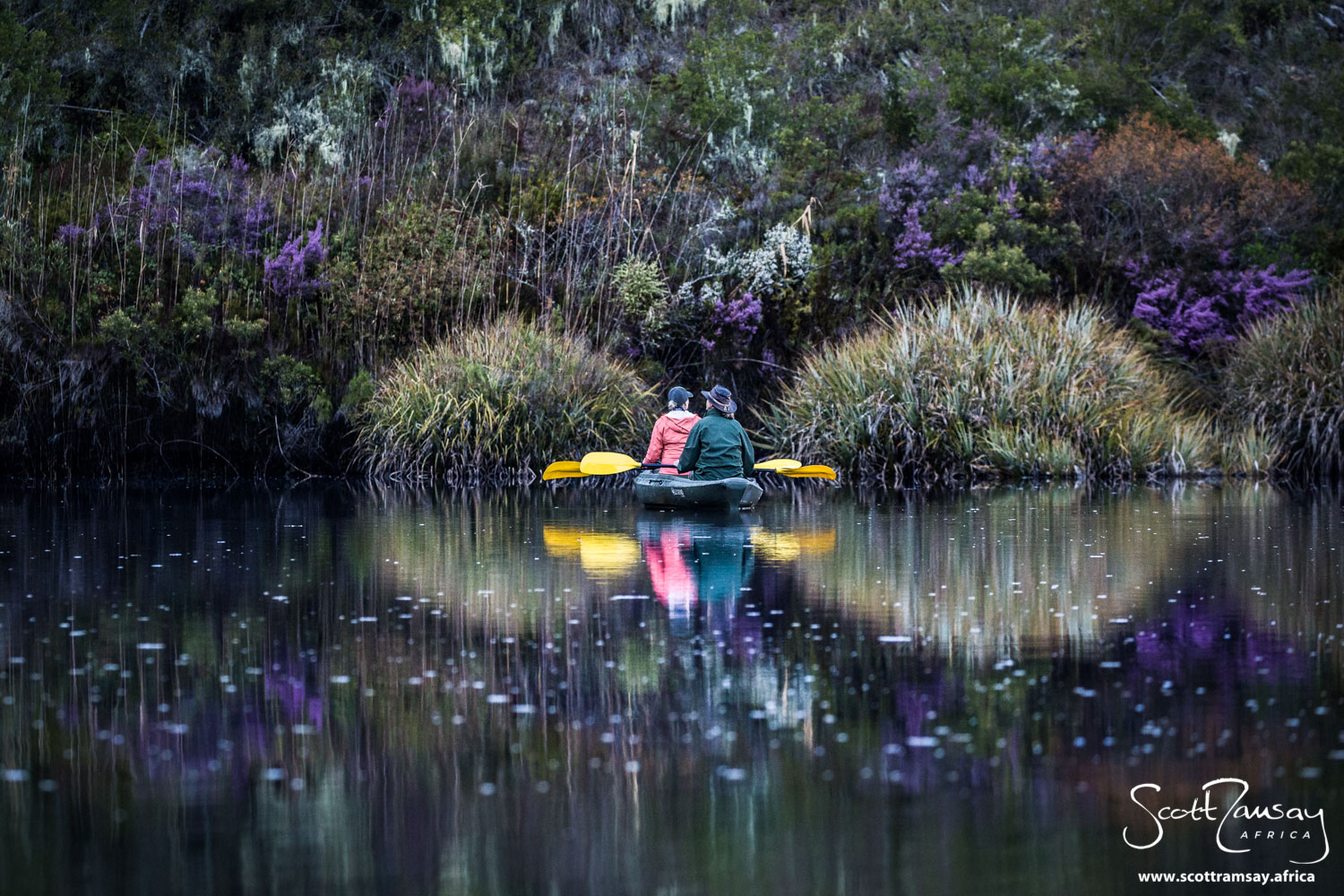My friends Michelle and Helen floating silently on the river's still waters, early one winter morning. Look at the colour tones of the fynbos on the banks!